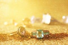 Η εικόνα των κομψών χρυσών δαχτυλιδιών στο χρυσό ακτινοβολεί υπόβαθρο Στοκ φωτογραφία με δικαίωμα ελεύθερης χρήσης