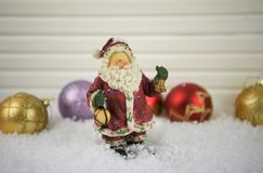 Η εικόνα φωτογραφίας Χριστουγέννων της παραδοσιακής διακόσμησης Άγιου Βασίλη στο χιόνι με κόκκινο και ο χρυσός ακτινοβολούν διακο στοκ φωτογραφία με δικαίωμα ελεύθερης χρήσης