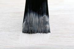 Η λειτουργώντας βούρτσα χρωματίζει ένα ξύλινο άσπρο χρώμα πατωμάτων Στοκ φωτογραφία με δικαίωμα ελεύθερης χρήσης