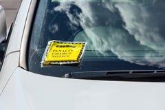 Η ειδοποίηση δαπανών ποινικής ρήτρας (πρόστιμο χώρων στάθμευσης) συνδέθηκε με το αλεξήνεμο του άσπρου αυτοκινήτου που στάθμευσαν  Στοκ Φωτογραφίες