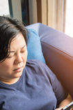 Η δεκαετία του '40 γυναικών της Ασίας που κρατά το smartphone σκεπτόμενο στον καναπέ στοκ φωτογραφία
