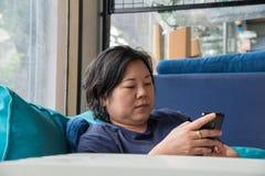 Η δεκαετία του '40 γυναικών της Ασίας που κρατά το smartphone σκεπτόμενο στον καναπέ στοκ φωτογραφία με δικαίωμα ελεύθερης χρήσης
