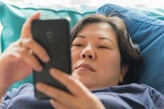 Η δεκαετία του '40 γυναικών της Ασίας που κρατά το smartphone σκεπτόμενο στον καναπέ στοκ εικόνα με δικαίωμα ελεύθερης χρήσης