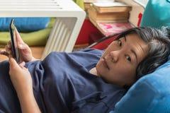 Η δεκαετία του '40 γυναικών της Ασίας που κρατά το smartphone σκεπτόμενο στον καναπέ στοκ φωτογραφίες με δικαίωμα ελεύθερης χρήσης