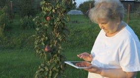 Η δεκαετία του '80 ηλικιωμένων γυναικών που κρατά μια ψηφιακή ταμπλέτα υπαίθρια απόθεμα βίντεο