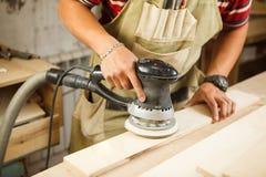 Η εκκεντρική αλέθοντας μηχανή κάνει την ξύλινη στίλβωση της σανίδας φραγμών στοκ εικόνα
