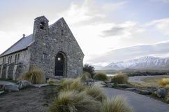 Η εκκλησία του καλού ποιμένα είναι τοποθετημένη στις ακτές της λίμνης Tekapo μεταξύ της φυσικής ομορφιάς της λίμνης και των βουνώ στοκ εικόνα με δικαίωμα ελεύθερης χρήσης