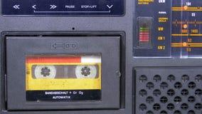Η εκλεκτής ποιότητας κίτρινη ακουστική κασέτα στο παλαιό όργανο καταγραφής ταινιών περιστρέφεται φιλμ μικρού μήκους