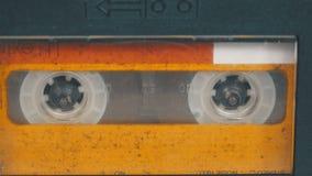 Η εκλεκτής ποιότητας κίτρινη ακουστική κασέτα στο όργανο καταγραφής ταινιών περιστρέφεται απόθεμα βίντεο