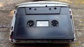 Η εκλεκτής ποιότητας μαύρη ακουστική κασέτα στο όργανο καταγραφής ταινιών περιστρέφεται απόθεμα βίντεο