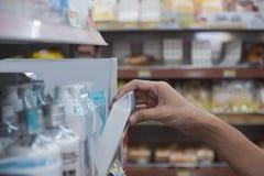 Η εκλεκτική εστίαση του ανθρώπινου χεριού ` s παίρνει τα προϊόντα ομορφιάς από το ράφι χάλυβα στο κατάστημα ψωνίζοντας λευκή γυνα στοκ φωτογραφία με δικαίωμα ελεύθερης χρήσης