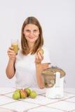 Η εκμετάλλευση κοριτσιών έκανε πρόσφατα το χυμό σε ένα χέρι και ένα αχλάδι σε άλλο Στοκ φωτογραφία με δικαίωμα ελεύθερης χρήσης