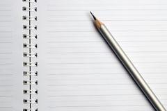 η εκπαίδευση έννοιας βιβλίων απομόνωσε παλαιό Άσπρο σημειωματάριο με το ασημένιο μολύβι στοκ εικόνα με δικαίωμα ελεύθερης χρήσης