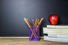 η εκπαίδευση έννοιας βιβλίων απομόνωσε παλαιό Μολύβι στον πίνακα και κόκκινο μήλο στο βιβλίο Στοκ εικόνες με δικαίωμα ελεύθερης χρήσης