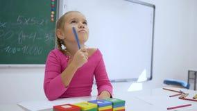 Η εκπαίδευση των παιδιών, μαθήτρια γράφει έναν στόχο στη συνεδρίαση copybook στο γραφείο σε μια τάξη στο υπόβαθρο του πίνακα απόθεμα βίντεο