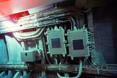 Ηλεκτρικά καλώδια και κιβώτια σε έναν βρώμικο συμπαγή τοίχο Στοκ Φωτογραφία