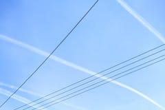 Ηλεκτρικά καλώδια που κρεμούν πέρα από τον ουρανό και τις λουρίδες από ένα αεροσκάφος αναχώρησης Στοκ φωτογραφία με δικαίωμα ελεύθερης χρήσης