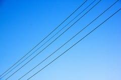 Ηλεκτρικά καλώδια που τεντώνουν πέρα από το μπλε ουρανό Στοκ Εικόνες