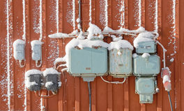 Ηλεκτρικά κιβώτια συνδέσεων με το χιόνι, αναδρομικό ύφος στον κόκκινο τοίχο στοκ εικόνα