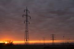 Ηλεκτρικοί πόλοι στο ηλιοβασίλεμα Στοκ Εικόνα