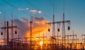 Ηλεκτρικός υποσταθμός διανομής με τα ηλεκτροφόρα καλώδια και τους μετασχηματιστές, στο ηλιοβασίλεμα Στοκ Φωτογραφία