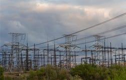 Ηλεκτρικός υποσταθμός διανομής με τα ηλεκτροφόρα καλώδια και τους μετασχηματιστές, στο ηλιοβασίλεμα Στοκ Εικόνες