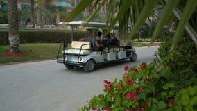 Ηλεκτρικό αυτοκίνητο τουριστών με τους ανθρώπους στο ξενοδοχείο φιλμ μικρού μήκους