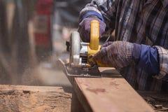 Ηλεκτρικό πριόνι χρήσης ξυλουργών να πριονίσει το ξύλο Στοκ Εικόνες