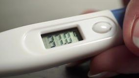 Ηλεκτρονικό ιατρικό θερμόμετρο στα όμορφα χέρια γυναικών 2 στενά επάνω βίντεο σε 1 απόθεμα βίντεο