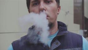 Ηλεκτρονικό τσιγάρο καπνού ατόμων υπαίθριο Vaper ατμός κίνηση αργή φιλμ μικρού μήκους