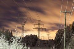 Ηλεκτροφόρα καλώδια και κίτρινα σύννεφα τη νύχτα Στοκ Εικόνες