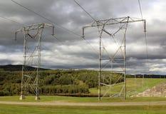 Ηλεκτροφόρα καλώδια σε έναν γκρίζο ουρανό με τα βουνά Στοκ Εικόνες