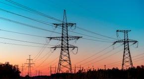 Ηλεκτροφόρα καλώδια σε μια ζωηρόχρωμη ανατολή, γραμμές ηλεκτρικής δύναμης ενάντια στον ουρανό στην ανατολή Στοκ Φωτογραφία