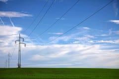 Ηλεκτροφόρο καλώδιο στη μέση ενός πράσινου τομέα με το μπλε ουρανό Στοκ φωτογραφία με δικαίωμα ελεύθερης χρήσης