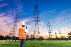 Ηλεκτρολόγος μηχανικός με τον πυλώνα ηλεκτρικής ενέργειας υψηλής τάσης στο sunri Στοκ Φωτογραφία