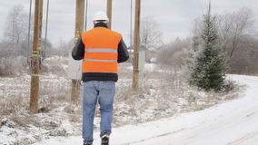Ηλεκτρολόγος μηχανικός με το τηλέφωνο κυττάρων στο δρόμο το χειμώνα απόθεμα βίντεο