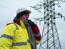 Ηλεκτρολόγος μηχανικός που μιλά στα πλέγματα τηλεφωνικής δύναμης στο υπόβαθρο Στοκ Φωτογραφία