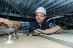 Ηλεκτρολόγος που εργάζεται με τα ηλεκτρικά καλώδια στο εργοστάσιο στοκ φωτογραφία