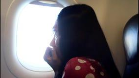 Η εκφοβισμένη γυναίκα φαίνεται έξω το αεροπλάνο παραθύρων απόθεμα βίντεο