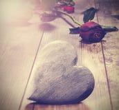 Η εκλεκτής ποιότητας εικόνα της καρδιάς σε ένα ξύλινο υπόβαθρο με το κόκκινο αυξήθηκε Β Στοκ Εικόνα