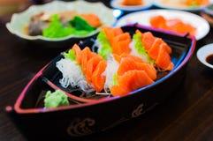 Η εκλεκτική εστίαση ακατέργαστο φρέσκο sashimi εξυπηρετεί σε ένα κύπελλο βαρκών με το W Στοκ Φωτογραφίες