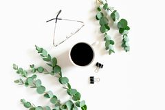 Η ελάχιστη σύνθεση με την κούπα του καφέ, συνδετήρες εγγράφου, γυαλιά, ευκάλυπτος διακλαδίζεται στοκ φωτογραφίες