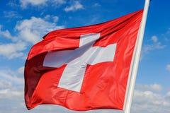 Η ελβετική σημαία κυματίζει στον αέρα ενάντια σε έναν μπλε ουρανό με clo στοκ φωτογραφίες