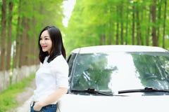 Η ελεύθερη στάση γυναικών carelss ευτυχής με ένα άσπρο αυτοκίνητο, ασφαλής έννοια κίνησης, απολαμβάνει την άνετη άνετη ζωή στοκ φωτογραφίες