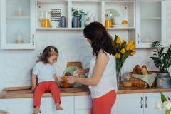 Η ελκυστικές νέες γυναίκα και λίγη χαριτωμένη κόρη μαγειρεύουν στην κουζίνα στοκ εικόνα