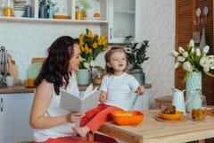 Η ελκυστικές νέες γυναίκα και λίγη χαριτωμένη κόρη μαγειρεύουν στην κουζίνα στοκ εικόνα με δικαίωμα ελεύθερης χρήσης