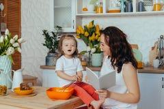 Η ελκυστικές νέες γυναίκα και λίγη χαριτωμένη κόρη μαγειρεύουν στην κουζίνα στοκ εικόνες