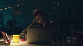 Η ελκυστική αποτελεσματική εργασία εργαζομένων γραφείων σκληρά στο γραφείο του αργά τη νύχτα, πίνει το τσάι και προγραμματισμός κ απόθεμα βίντεο
