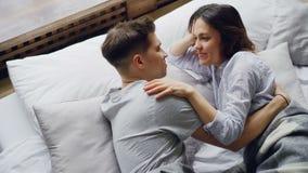 Η ελκυστική ασιατική γυναίκα βρίσκεται στο κρεβάτι με το φίλο της σχετικά με την τρίχα του και σώμα ενώ την αγκαλιάζει, είναι φιλμ μικρού μήκους