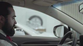 Η ελκυστική βέβαια γενειοφόρος συνεδρίαση επιχειρηματιών πορτρέτου στο όχημα και επιθεωρεί το πρόσφατα αγορασμένο αυτοκίνητο από  φιλμ μικρού μήκους